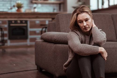 woman sitting on floor needing Self-Harm Therapy