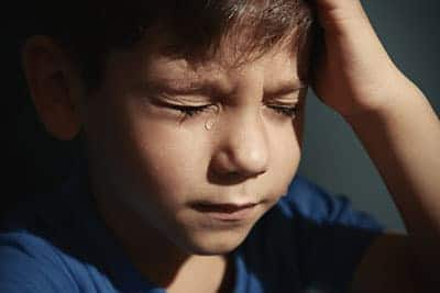 a child crying from childhood abuse before going to a childhood abuse treatment center
