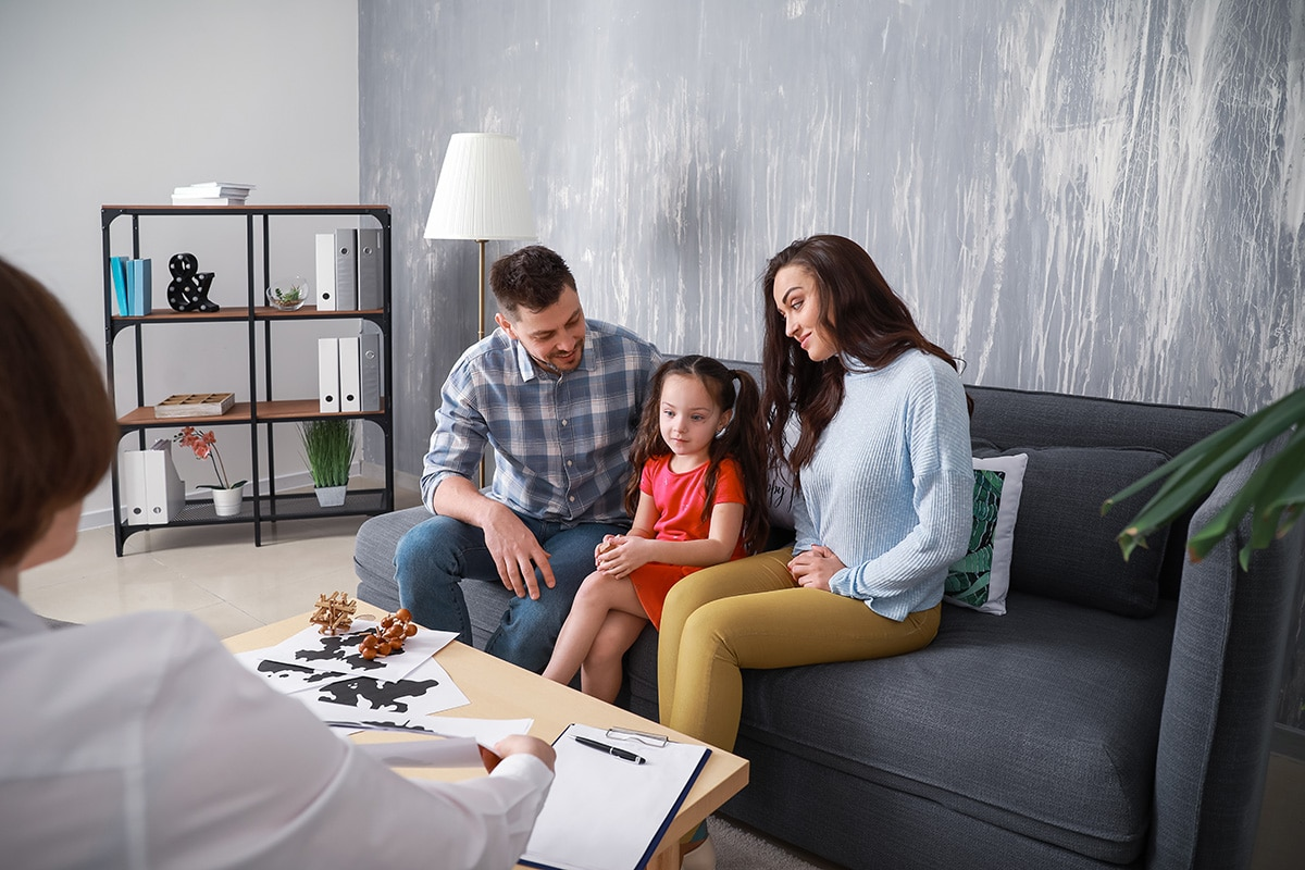 A mother, father, and daughter talk to a therapist about when to seek family therapy