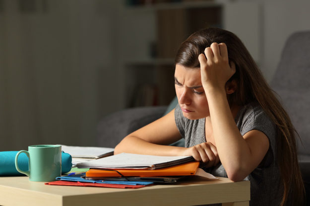 student looking at papers coping with anxiety