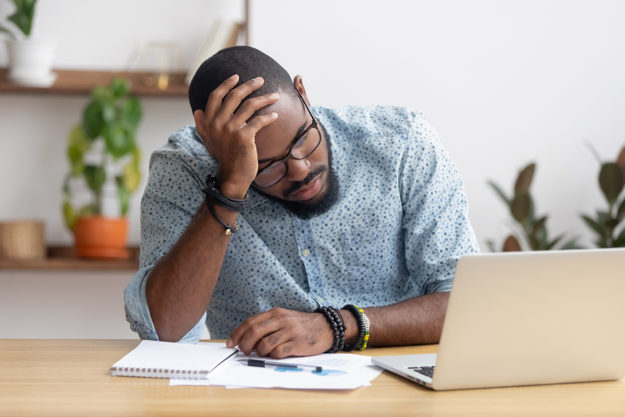 man researching at computer frustrated coping with job loss