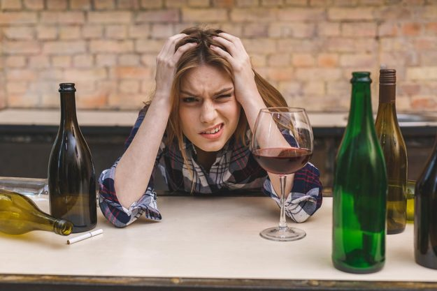 woman surrounded by alcohol bottles showing the risks of alcohol abuse
