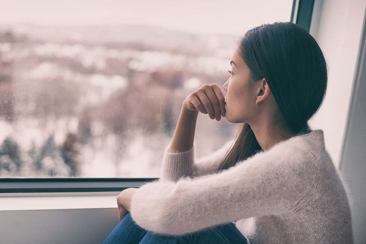 woman looking out window dealing with seasonal depression